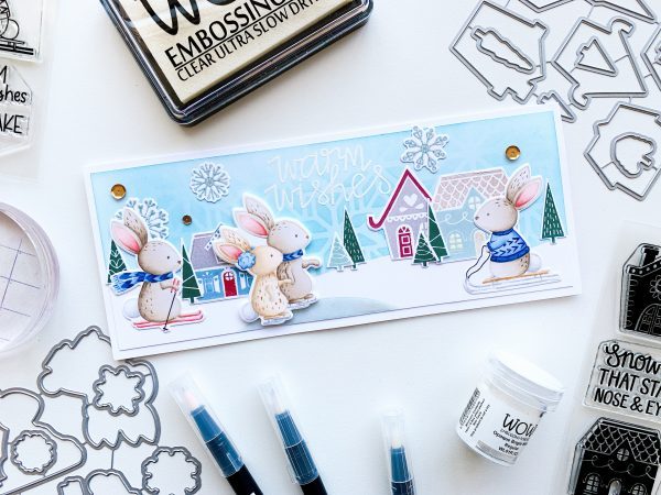 Winter card with bunnies doing winter sports and nordic village