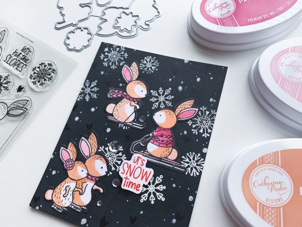bunnies skiing and ice skating on handmade card with snowflakes