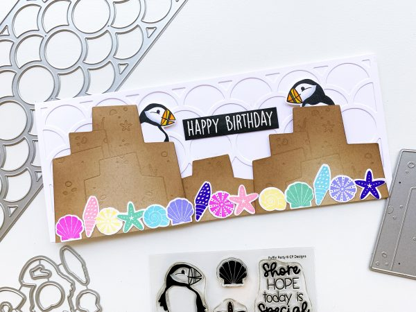 slimline hand made card with puffins behind rocks with rainbow shells