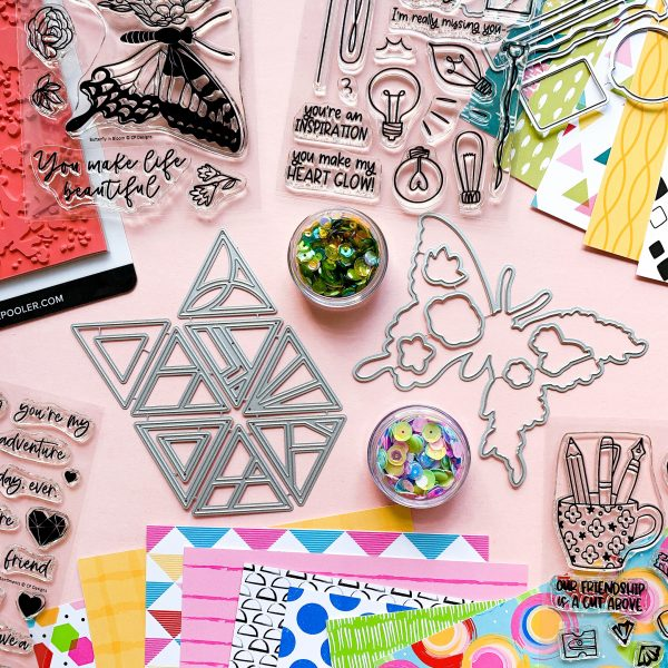 collection of stamps, dies, paper and sequins for paper crafting